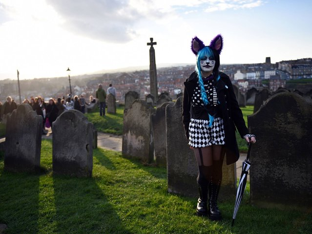 "A woman dressed in a costume is pictured during the biannual ""Whitby Goth Weekend"" (WGW) festival in Whitby, Northern England, on November 2, 2014. The WGW festival brings thousands of goths and alternative lifestyle fans from the UK and around the world over a weekend of music, dancing and shopping. (Photo by Oli Scarff/AFP Photo)"