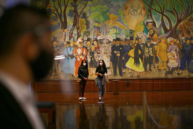 """Visitors, wearing protective face masks, look at artworks in front of vast mural created by Diego Rivera """"Dream of a Sunday Afternoon in the Alameda Central"""" at the Diego Rivera Mural Museum, as the museum re-opens doors to the public following the coronavirus disease (COVID-19) outbreak in Mexico City, Mexico on September 2, 2020. (Photo by Edgard Garrido/Reuters)"""