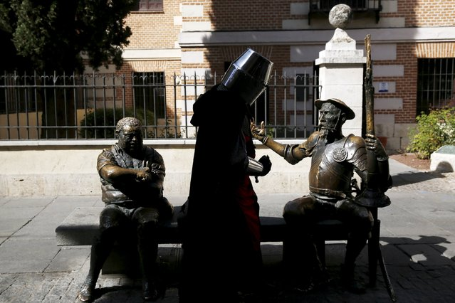 """An actor performing as a knight stands next to statues of Don Quixote (R) and Sancho Panza, the two main characters from the famous novel by Spanish writer Miguel de Cervantes, """"Don Quixote"""", during the annual Cervantes market (Mercado Cervantino) in Cervantes' hometown Alcala de Henares, Spain, October 9, 2015. (Photo by Susana Vera/Reuters)"""