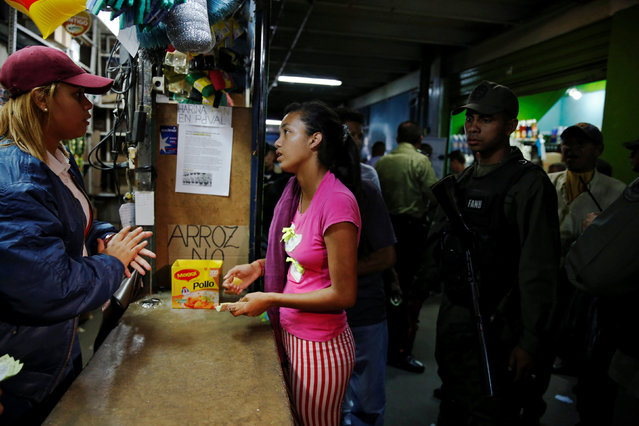 A woman talks to a seller as she buys basic food during a special inspection of Venezuelan soldiers to a municipal market in Caracas, Venezuela July 15, 2016. (Photo by Carlos Garcia Rawlins/Reuters)