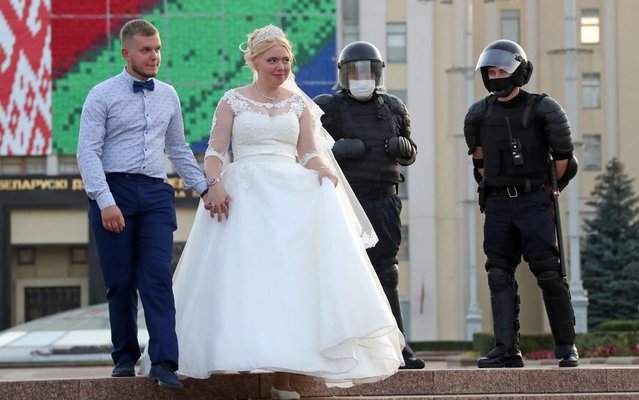Newlyweds and police officers during a women's rally in Independence Avenue in Minsk, Belarus on September 5, 2020. Since the announcement of the 2020 Belarusian presidential election results on August 9, mass protests against the election results have been erupting in major cities across Belarus. (Photo by Valery Sharifulin/TASS)
