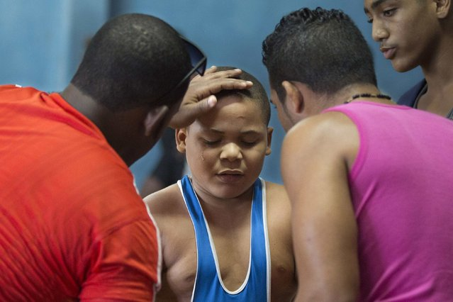 A child cries next to his coaches after losing a fight at a local wrestling tournament in Havana, November 1, 2014. (Photo by Alexandre Meneghini/Reuters)