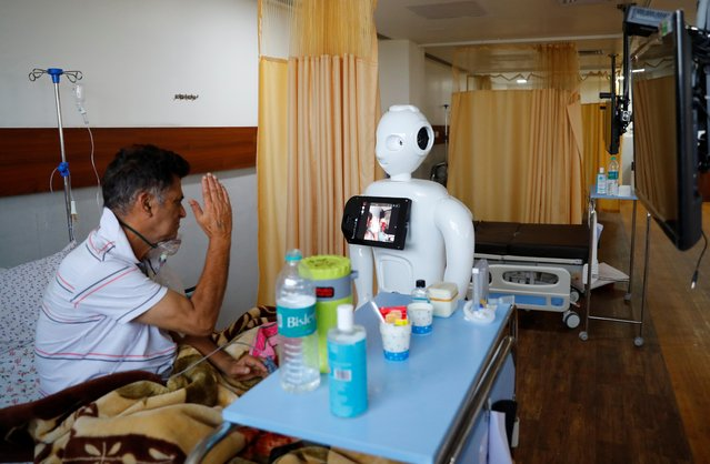 "A patient suffering from the coronavirus disease (COVID-19) speaks to his family members, using a robot named ""Mitra"" at the Intensive Care Unit (ICU) of the Yatharth Super Speciality Hospital in Noida, on the outskirts of New Delhi, India, September 15, 2020. (Photo by Adnan Abidi/Reuters)"
