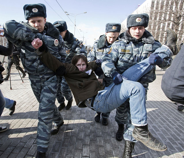"Policemen detain an opposition supporter taking part in a picketing calling for the release of two jailed members of the p*ssy Riot protest punk band in central Moscow on March 8, 2013. Nadezhda Tolokonnikova, a philosophy student, was sent to prison camp in October 2012 along with bandmate Maria Alyokhina, after being convicted of hooliganism motivated by religious hatred for singing a ""punk prayer"" in a Moscow cathedral protesting President Vladimir Putin's close links with the Russian Orthodox Church. (Photo by Evgeny Feldman/AFP Photo)"
