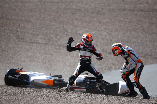 Mahindra Moto3 rider Bryan Schouten of the Netherlands fights with compatriot Kalex KTM Moto3 rider Scott Deroue (R) after they crashed during the German Grand Prix at the Sachsenring circuit in Hohenstein-Ernstthal in this July 13, 2014 file photo. During lap 26, towards the end of the race, I was standing behind the tire barrier in the first bend waiting for the pack of riders. (Photo and caption by Thomas Peter/Reuters)