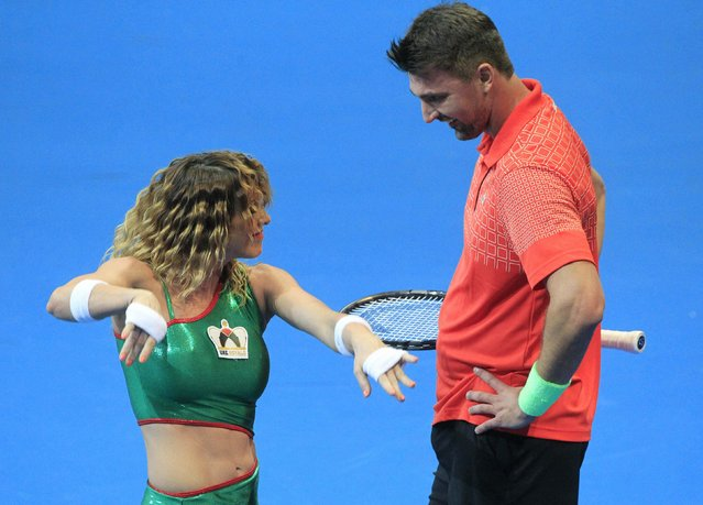 Goran Ivanesevic of the UAE Royals looks at a dancer performing in front of him during a break in his past champions' singles tennis match with Carlos Moya of the Manila Mavericks at the International Premier Tennis League (IPTL) competition in Manila November 28, 2014. (Photo by Romeo Ranoco/Reuters)