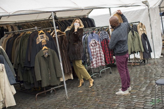 "A customer, wearing a face mask to fight against the spread of the coronavirus, tries on a coat at Marolles flea market in Brussels, Tuesday, October 13, 2020. Authorities in Belgium, one of the European countries hit hardest by the coronavirus, are warning that the number of cases is rising at a ""quite alarming"" rate and that 10.000 people could be catching the virus each day by the end of the week. (Photo by Francisco Seco/AP Photo)"