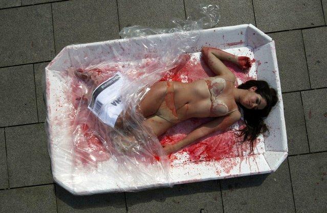 A ativista posou apenas de calcinha e sutiã, com o que aparenta ser sangue falso sobre o corpo (Foto by Albert Gea/Reuters)