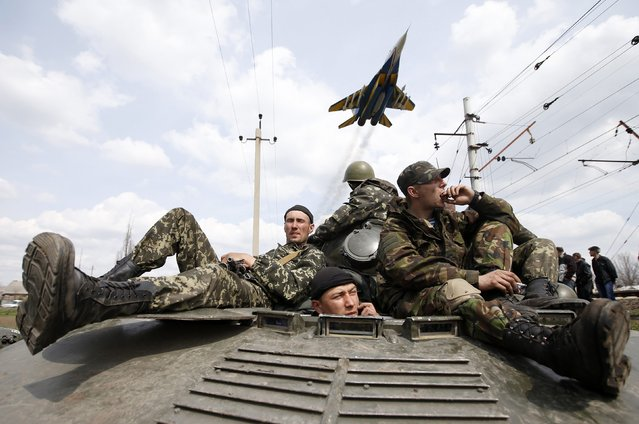 A fighter jet flies above as Ukrainian soldiers sit on an armoured personnel carrier in Kramatorsk, in eastern Ukraine, in this April 16, 2014 file photo. (Photo by Marko Djurica/Reuters)