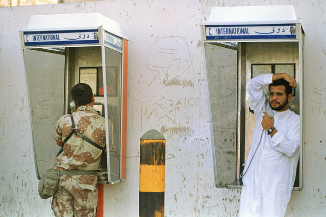 Chief Warrant Officer 2 James Rathburn, Colorado Springs, Colo., a member of the 544th Maintenance Battalion based in Ft. Carson, Colo., left, and an unidentified man place calls from neighboring phone booths in a Saudi town, December 12, 1990. (Photo by Peter Dejong/AP Photo)