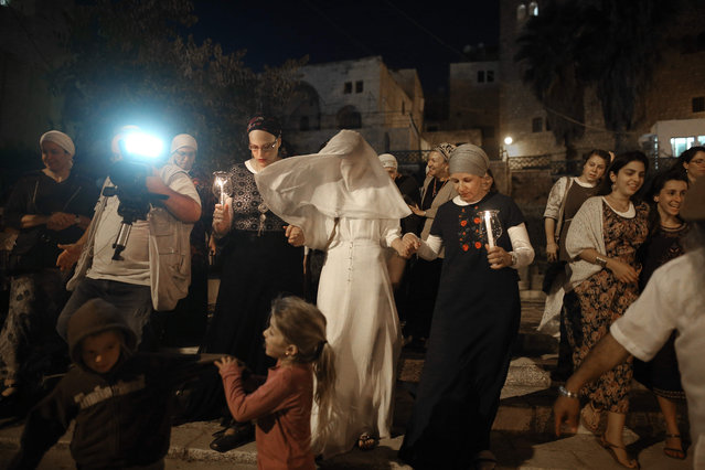Israeli settler bride Yael Levi is escorted by friends and relatives during her wedding ceremony at the plaza outside the Cave of the Patriarchs also known as the Ibrahimi Mosque, which is a holy shrine for Jews and Muslims, in the heart of the divided city of Hebron in the southern West Bank, on September 22, 2016. (Photo by Menahem Kahana/AFP Photo)