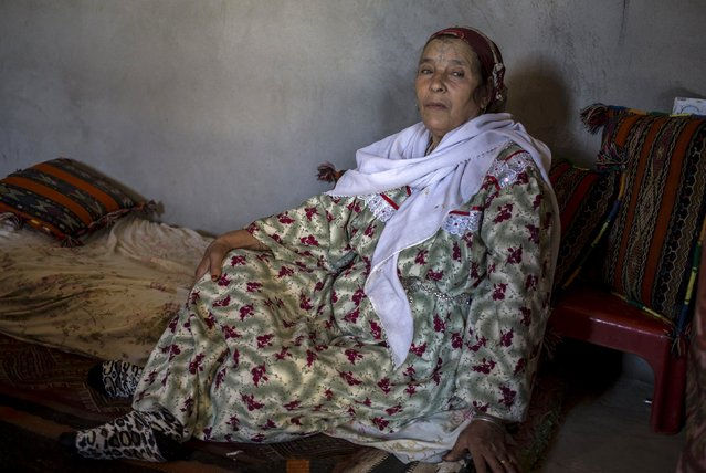"""Khamsaa Hougali, 68, a berber woman from the Chaouia region, who has facial tattoos, sits inside her house in Bouhmama near the eastern city of Khenchela, Algeria October 10, 2015. Among the Chaouia people of the Aures mountains, a woman's beauty used to be judged by her tattoos. """"In my case it was different. My stepmother advised me to get tattooed to bring luck after the sudden death of my first three children. My cousin and sister-in-law tattooed me. (Photo by Zohra Bensemra/Reuters)"""
