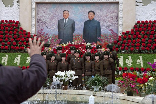 A North Korean portrait photographer instructs North Korean soldiers to pose for a picture under a mosaic of the late leaders Kim Il Sung and Kim Jong Il at an exhibition in Pyongyang on Sunday, February 17, 2013 where Kimjongilia flowers, named after Kim Jong Il, were on display. (Photo by David Guttenfelder/AP Photo)