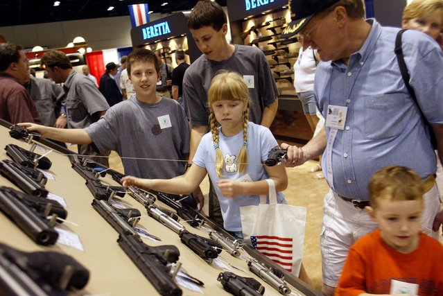 Members of a family check out the Beretta gun display at the 132nd Annual National Rifle Association Meeting in Orlando, Florida, April 27, 2003. The National Rifle Association had plenty to celebrate at its annual convention on Sunday: a gun-friendly president and Congress it helped elect, a robust membership of four million and a real shot at eliminating its most hated law – the ban on assault weapons. (Photo by Shannon Stapleton/Reuters)