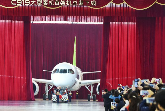 People take pictures and videos as the first C919 passenger jet made by the Commercial Aircraft Corp of China (Comac) is pulled out during a news conference at the company's factory in Shanghai, November 2, 2015. Comac rolled out China's first homemade 158-seated C919 narrow body jet, which is meant to rival similar models from Airbus Group and Boeing Co. (Photo by Reuters/Stringer)