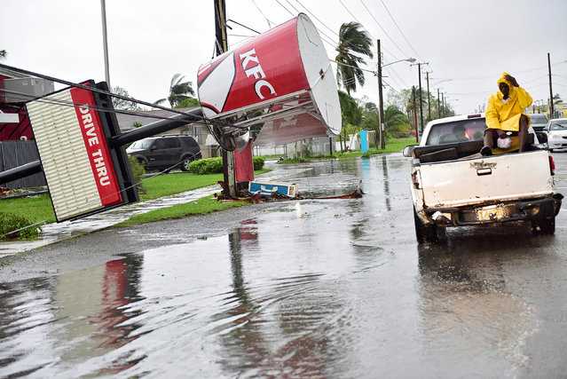 A KFC sign damaged by Hurricane Matthew is supported by utility lines on Carmichael Road in Nassau, Bahamas October 6, 2016. (Photo by Dante Carrer/Reuters)