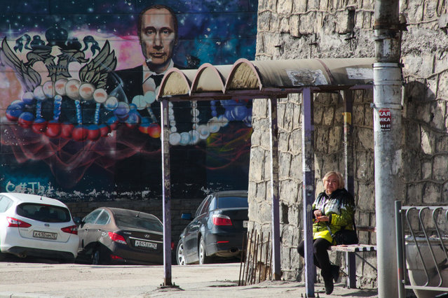 A woman waits at a bus stop in front of a graffiti depicting Russian President Vladimir Putin on a building in Sevastopol, Crimea, on March 12, 2018. Russia will vote for President on March 18, 2018. (Photo by AFP Photo/Stringer)