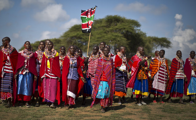 A group of Maasai women arrive to support the young warriors from their village at the annual Maasai Olympics in the Sidai Oleng Wildlife Sanctuary near to Mt Kilimanjaro, in southern Kenya Saturday, December 13, 2014. (Photo by Ben Curtis/AP Photo)