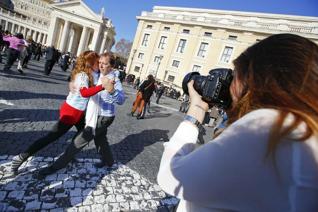 A woman takes a picture of a couple tango dancing in front of Saint Peter's basilica at the Vatican, December 17, 2014. (Photo by Tony Gentile/Reuters)