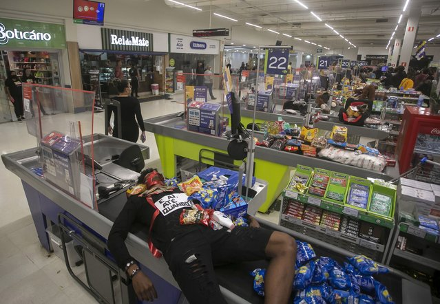 Jonata Anjo lies on a checkout counter at a Carrefour supermarket during a protest against the murder of Black man Joao Alberto Silveira Freitas at a different Carrefour supermarket the night before, on Brazil's National Black Consciousness Day in Rio de Janeiro, Brazil, Friday, November 20, 2020. (Photo by Bruna Prado/AP Photo)