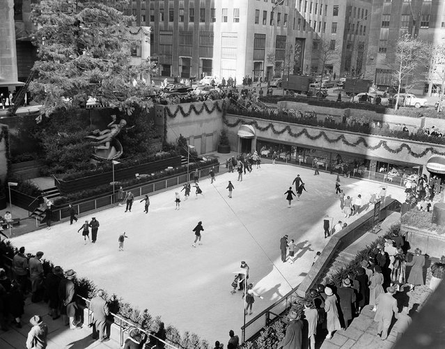 With the famed Rockefeller Center Christmas tree rising above them, skaters glide on the ice at the center's skating rink in midtown Manhattan, New York,  in this photo from December 8, 1949. The skating rink turns 70 on Christmas Day, 2006. (Photo by John Lindsay/AP Photo)