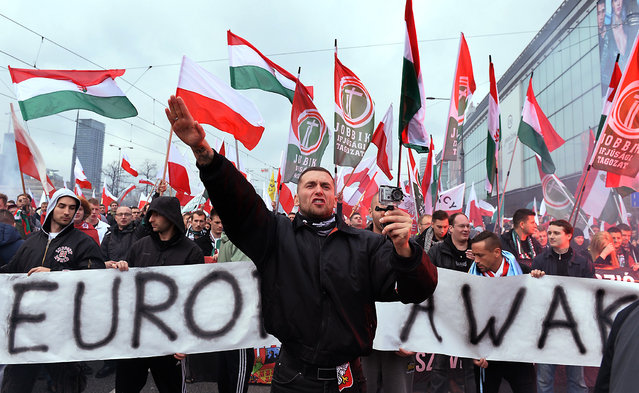 "A demonstrator shouts and performs a Nazi salute in front of banner reading ""Europe awake"" followed by a group of Hungarian Jobbik party representatives during an annual march commemorating Poland's National Independence Day in Warsaw on November 11, 2015. Poland's National Independence Day commemorates the anniversary of the Restoration of a Polish State in 1918. (Photo by Janek Skarzynski/AFP Photo)"