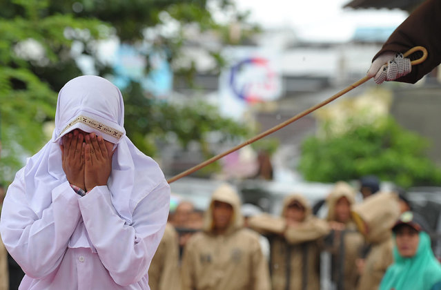 A Muslim woman gets caned 23 strokes after being caught in close proximity with her boyfriend in Banda Aceh on October 17, 2016. (Photo by Chaideer Mahyuddin/AFP Photo)