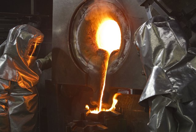 Workers in protective suits pour out the melted gold of a crucible in forms. March 14, 2013; Tien Shan mountains, Kyrgyzstan. (Photo by Shamil Zhumatov/Reuters)