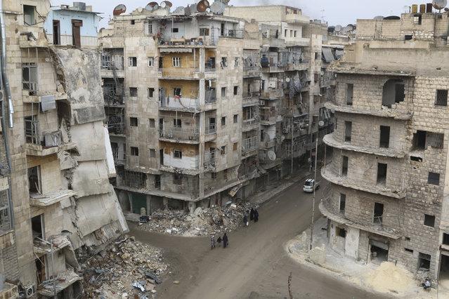 People walk past damaged buildings in Aleppo's al-Shaar district, December 10, 2014. (Photo by Mahmoud Hebbo/Reuters)