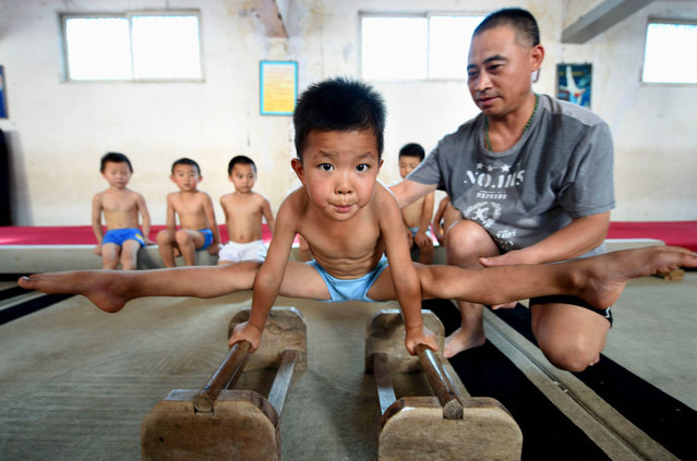 A young boy trains on the bars. (Photo by ChinaFotoPress/ChinaFotoPress via Getty Images)
