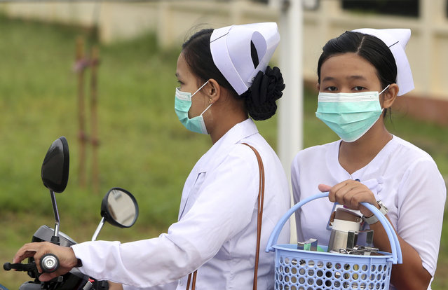 Nurses cover their faces with masks to protect from the spread of the swine flu outside the Naypyitaw hospital, Tuesday, July 25, 2017, in Naypyitaw, Myanmar. Public health officials in Myanmar say that H1N1 flu, also known as swine flu, has killed three people out of 13 confirmed cases of the infection. (Photo by Aung Shine Oo/AP Photo)