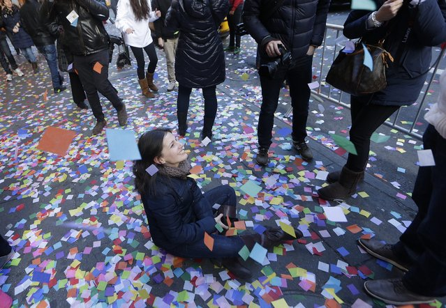 People watch at workers and the cast of Disney's Aladdin musical performing a Confetti Test as preparations are underway for the Times Square New Year's Eve celebration, on Times Square in New York, New York, USA, 29 December 2014. (Photo by Andrew Gombert/EPA)