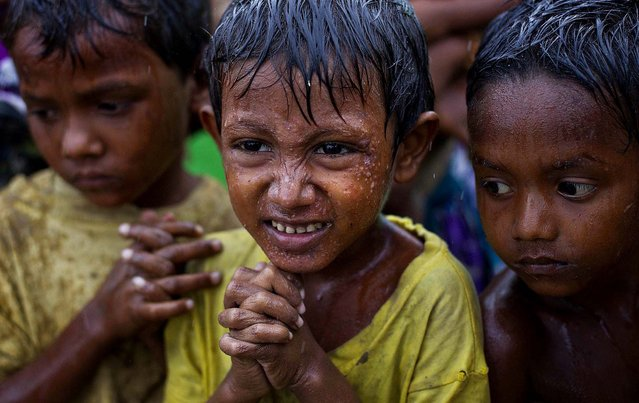 Internally displaced boys shiver in the rain in a makeshift camp for Rohingya people in Sittwe, Myanmar, as Cyclone Mahasen approaches, on May 14, 2013. The U.N. said the cyclone, expected later this week,  could swamp makeshift housing camps sheltering tens of thousands of Rohingya.  Myanmar state television reported Monday that 5,158 people were relocated from low-lying camps in Rakhine state to safer shelters, but far more people are considered vulnerable. (Photo by Gemunu Amarasinghe/Associated Press)