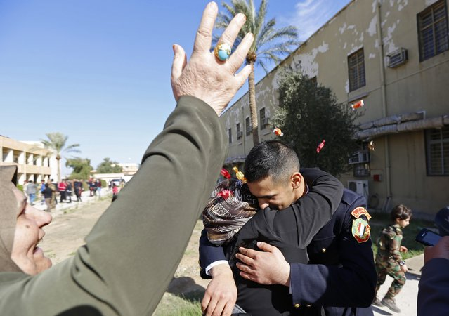 A family member hugs an officer at his graduation ceremony during Iraqi Army Day anniversary celebration in Baghdad January 6, 2015. (Photo by Thaier al-Sudani/Reuters)