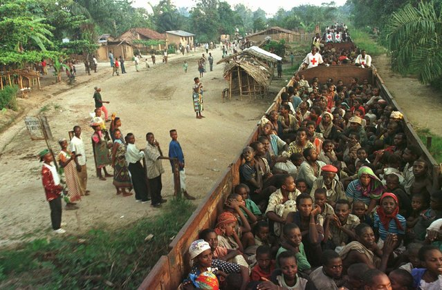 Zairian villagers watch as Hutu refugees are evacuated by train from the Biaro refugee camp south of Kisangani Tuesday, May 6, 1997. Tuesday the train evacuations began anew following Sunday's overcrowding accident in which 91 refugees were killed. (Photo by John Moore/AP Photo)