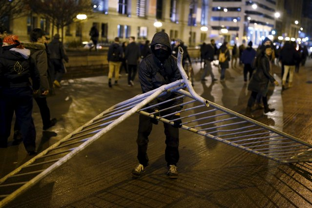 Protesters drag barricades onto Michigan Avenue to disrupt traffic during a protest in response to the fatal shooting of Laquan McDonald in Chicago, Illinois, November 25, 2015. (Photo by Andrew Nelles/Reuters)