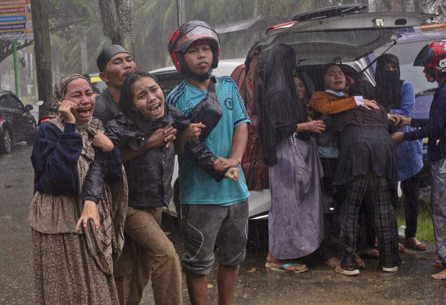 People react as the body of a relative is retrieved from the ruin of a building at an area affected by an earthquake in Mamuju, West Sulawesi, Indonesia, Friday, January 15, 2021. A strong, shallow earthquake shook Indonesia's Sulawesi island just after midnight Friday, toppling homes and buildings, triggering landslides and killing a number of people. (Photo by Yusuf Wahil/AP Photo)