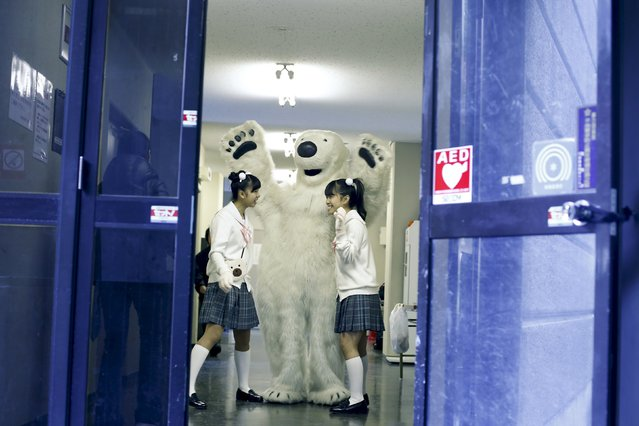 A man in a polar bear costume greet girls in school uniform before a performance at a protest organised by environment protection groups ahead of the 2015 Paris Climate Conference, known as the COP21 summit, in Tokyo, November 28, 2015. (Photo by Thomas Peter/Reuters)