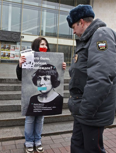 """A gay rights activist holds a board displaying 19th century Russian poet Marina Tsvetaeva during an unsanctioned protest rally to defend the rights of Russian gays and lesbians in St. Petersburg, in this April 7, 2012 file photo. Along with a planned new law banning the spread of gay """"propaganda"""" among minors, President Vladimir Putin has also overseen a religious revival that aims to give the Orthodox Church, whose leader has suggested that homosexuality is one of the main threats to Russia, a more public role as a moral authority. The number of documented cases of violence against gays in Russia is low. But there are no official figures on anti-gay crime in Russia, and gay rights campaigners say the numbers available mask the true number of attacks on gays, lesbians, bisexual and transgender people. Most go unreported, or are not classified as such by the police. (Photo by Alexander Demianchuk/Reuters)"""