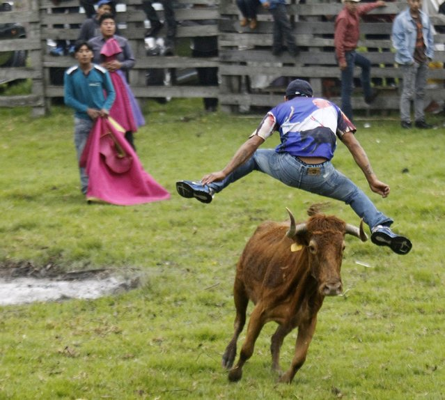 Ecuadorean spontaneous bullfighters participate in a popular bull festival called Las Canteras del Antisana at Pinantura village on the base of the Antisana volcano in Quito, November 28, 2015. (Photo by Guillermo Granja/Reuters)