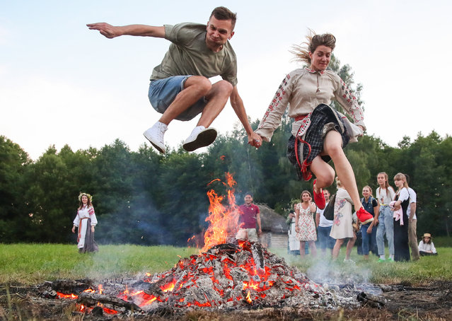 A man and a woman jump over a bonfire during Ivan Kupala Day celebrations held by the Belarusian State Museum of Folk Architecture and Rural Lifestyle in the village of Ozertso near Minsk, Belarus on July 4, 2020. Ivan Kupala Day, also known as Ivana-Kupala or Kupala Night, is a traditional pagan holiday celebrated in eastern Slavic cultures. Various rituals are traditionally performed on Kupala Night, including making flower wreaths, fortune-telling, jumping over bonfires, and burning a wheel-like effigy symbolizing the sun. (Photo by Natalia Fedosenko/TASS)