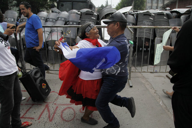 A couple dances in front of the police barricade during a protest in Tegucigalpa, Honduras, Saturday June 2, 2018. Members of the Opposition Alliance Against the Dictatorship marched the streets in protest of Juan Orlando Hernandez' government and were forcibly removed by military and police. (Photo by Fernando Antonio/AP Photo)