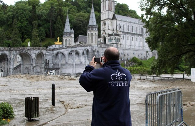 A guardian of Lourdes sanctuary takes photo of Lourdes  sanctuary flooding in Lourdes, southwestern France, Tuesday, June 18, 2013. French rescue services and police are evacuating hundreds of pilgrims from hotels threatened by floodwaters from a rain-swollen river in the Roman Catholic shrine town of Lourdes. (Photo by Bob Edme/AP Photo)