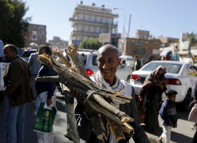 A man smiles as he carries firewood he bought on a street amid ongoing fuel and cooking gas shortages in Yemen's capital Sanaa December 2, 2015. (Photo by Khaled Abdullah/Reuters)