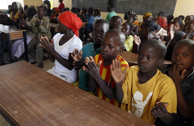 Children displaced as a result of Boko Haram attacks in the northeast region of Nigeria, clap during a class at Maikohi secondary school camp for internally displaced persons (IDP) in Yola, Adamawa State January 13, 2015. (Photo by Afolabi Sotunde/Reuters)