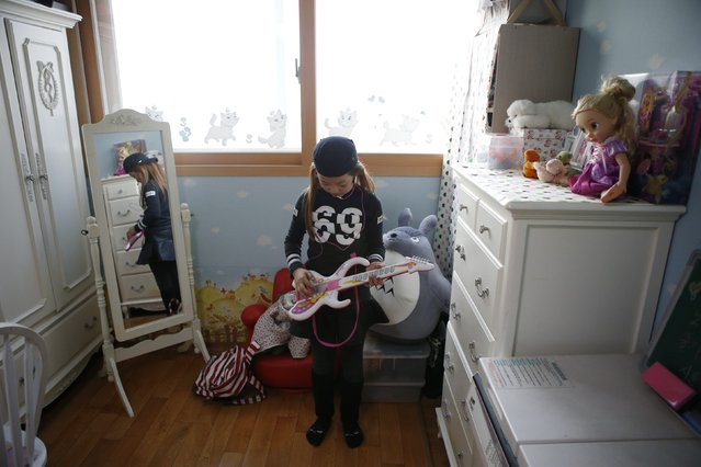 Kim Si-yoon plays a toy guitar at her house in Seoul November 20, 2014. (Photo by Kim Hong-Ji/Reuters)
