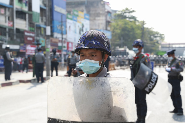 A policeman in riot gear stands guard during a protest rally in Yangon, Myanmar, on February 6, 2021. (Photo by AP Photo/Stringer)