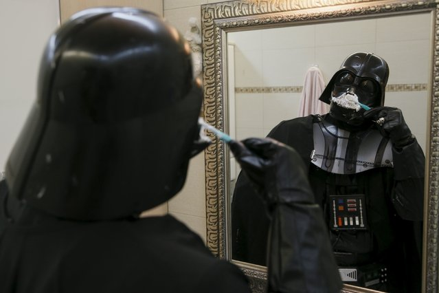 Darth Mykolaiovych Vader, who is dressed as the 'Star Wars' character Darth Vader, poses for a picture as he pretends to clean his teeth in the bathroom of his apartments in Odessa, December 2, 2015. (Photo by Valentyn Ogirenko/Reuters)