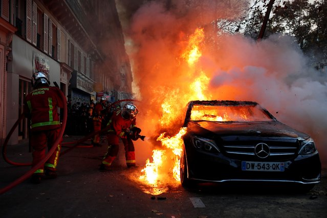 Fire-fighters pull off a fire on a burning car during a demonstration against a security law that would restrict sharing images of police, Saturday, November 28, 2020 in Paris. Civil liberties groups and journalists are concerned that the measure will stymie press freedoms and allow police brutality to go undiscovered and unpunished. The cause has gained fresh impetus in recent days after footage emerged of French police officers beating up a Black man, triggering a nationwide outcry. (Photo by Francois Mori/AP Photo)