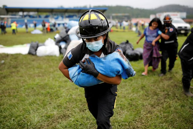 A firefighter carries a baby rescued along with her mother from an area affected by mudslides caused by Storm Eta, in San Cristobal Verapaz, Guatemala on November 7, 2020. (Photo by Luis Echeverria/Reuters)